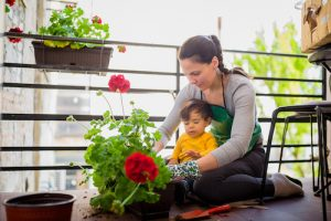 Woman taking care of her flowers at her home balcony while her baby boy is around.