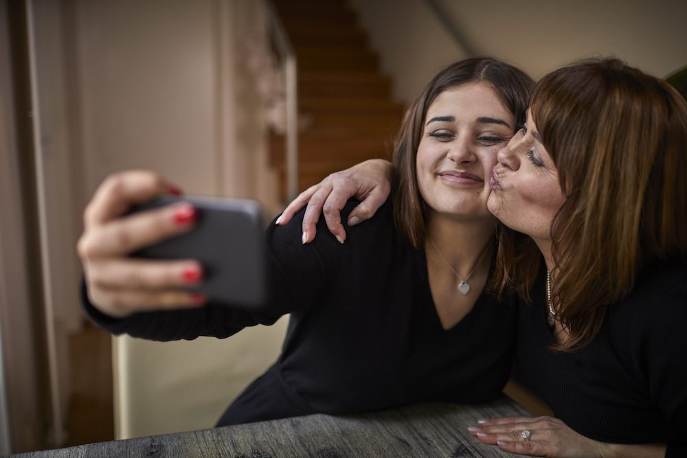 mother and daughter taking a selfie on a smart phone