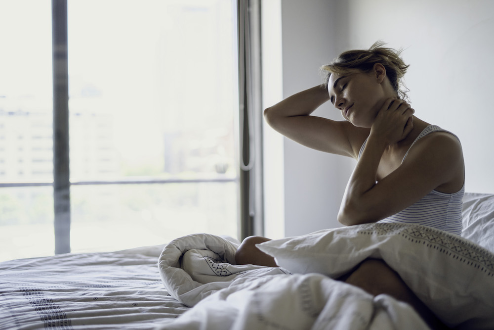 Young woman with eyes closed stretching her neck while sitting on bed in bedroom