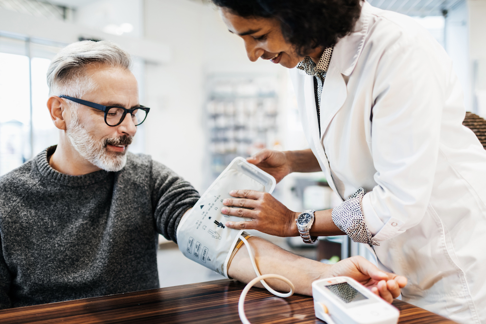 A pharmacist measuring a mature man's blood pressure using specialist equipment.