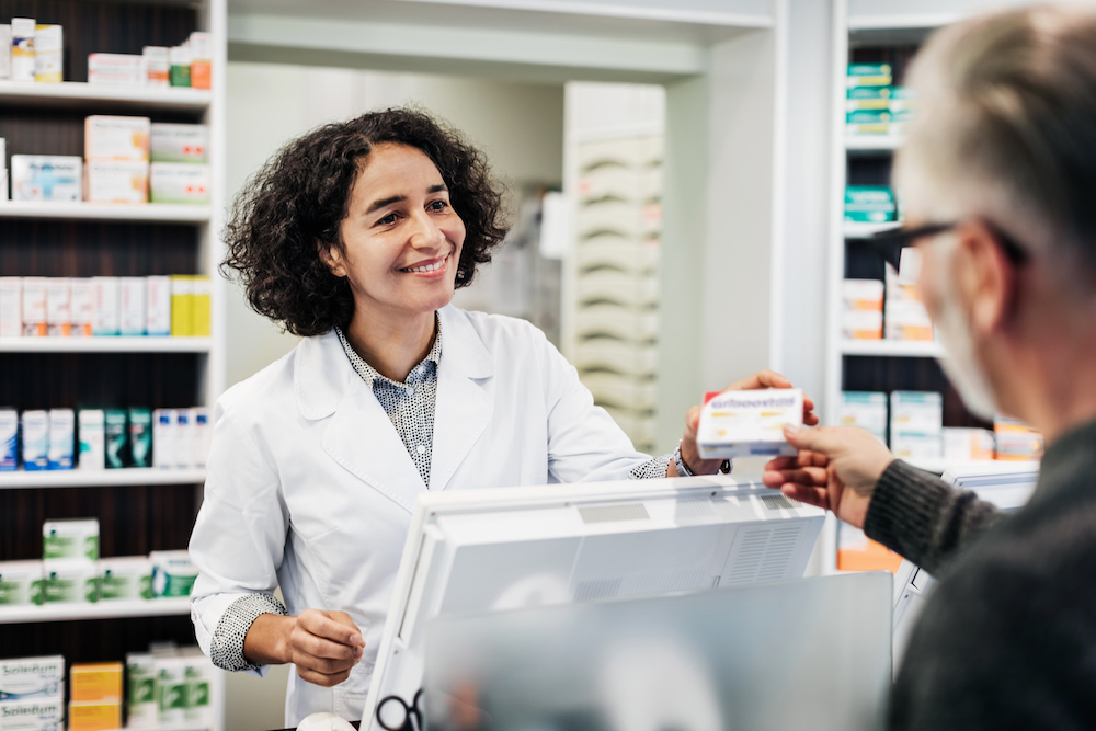 A pharmacist behind the counter, smiling while handing a customer his prescription medicine.