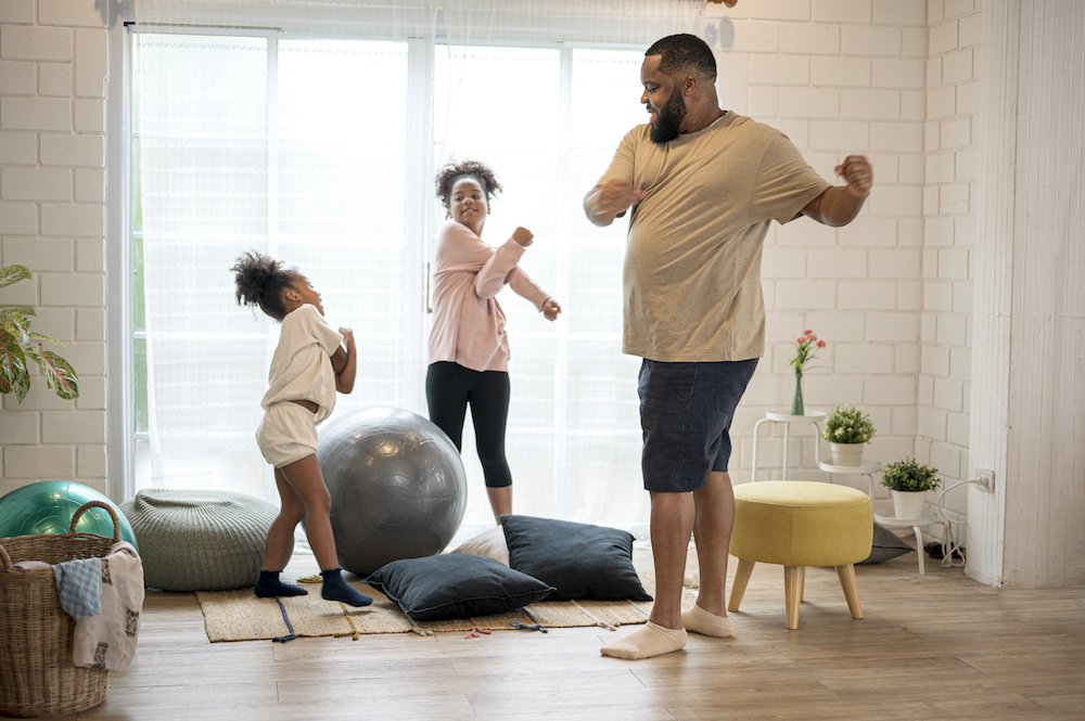 Father and his two daughter morning exercise at home.