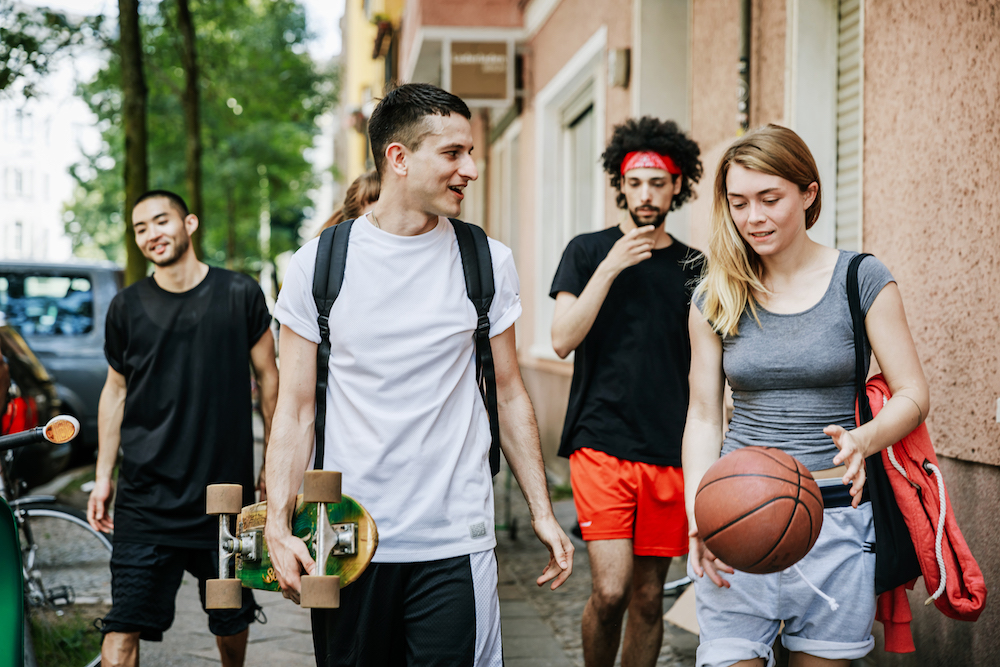 A young group of friends are walking home and chatting with each other after a day of playing basketball together.