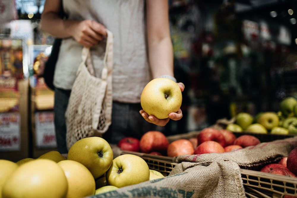Close up of young person shopping for fresh organic fruits in farmer's market with a cotton mesh eco bag.